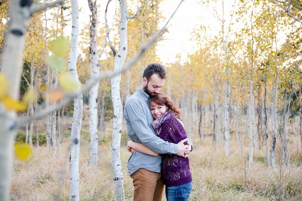engaged couple hugging by aspen trees